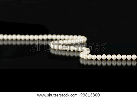 Single strand of white pearls reflected on black - stock photo