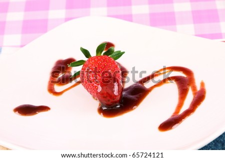 Single strawberry with brown sryup either chocolate vinegar or sauce