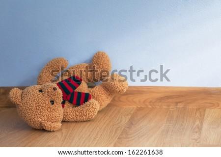Single teddy bear on a floor in a child room - stock photo