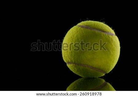 Single tennis ball isolated on black background - stock photo