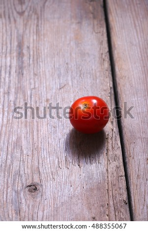 Single tomato on wooden background.