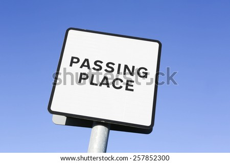 Single track road with passing places sign against a clear blue sky. - stock photo