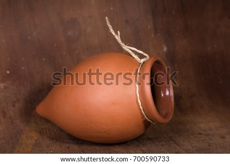 Single traditional clay jug on wooden background