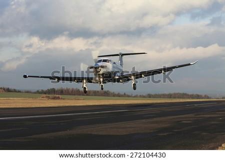 Single turboprop aircraft landing on runway, shoted on airport Pribram - stock photo