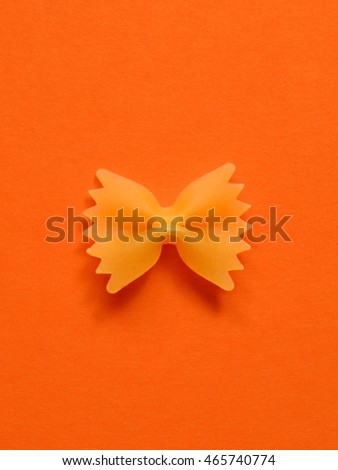single uncoocked farfalle pasta on orange colored  background