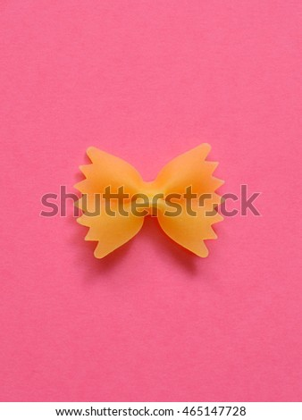 single uncoocked farfalle pasta on pink background