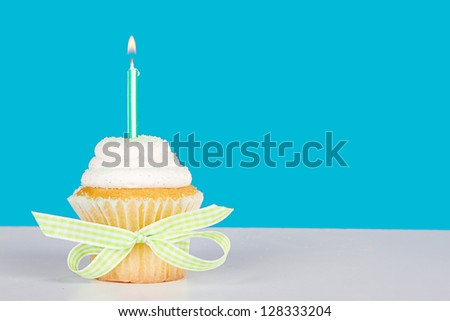 Single vanilla cupcake with lit green candle and sprinkles on a blue background and white table - stock photo
