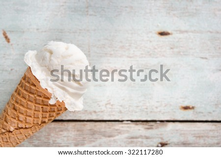 Single vanilla ice cream in a waffle cones over wooden background. - stock photo