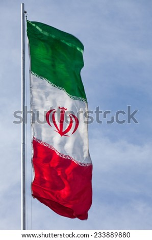 Single vertical Iranian flag waving in the wind against blue sky with copy space on the right. - stock photo
