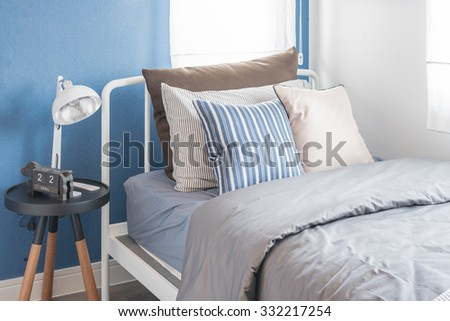 single white bed with white lamp and blue wall in kid's bedroom - stock photo