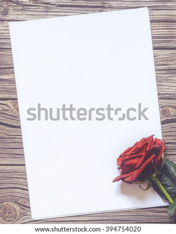Single white blank paper with copy space on table with weathered wooden surface next to one stemmed red rose - stock photo