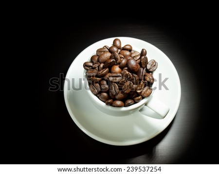 Single white coffee cup full of whole roasted coffee beans. - stock photo