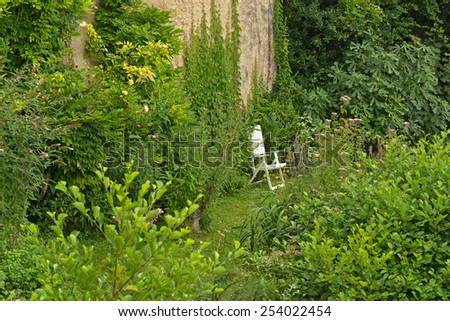 Single White Folding Lawn Chair Hidden by Lush Green Vegetation in Garden of Home - stock photo