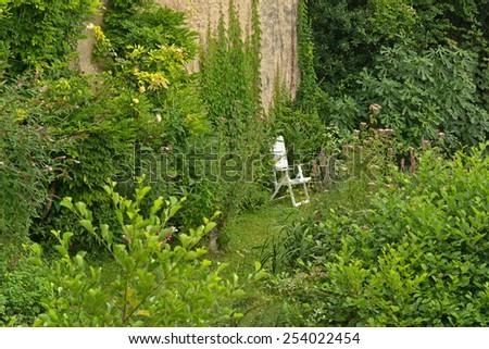 Single White Folding Lawn Chair Hidden by Lush Green Vegetation in Garden of Home - stock photo