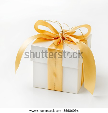 Single white gift box with gold ribbon on white background. - stock photo