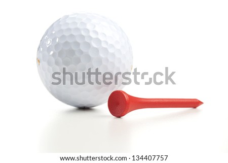 Single white golf ball and a single tee. Close up shot with shallow depth of field.
