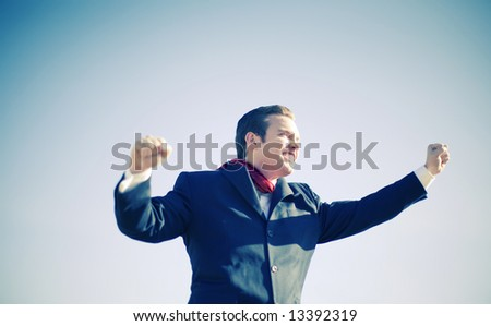 single white handsome young businessman in full suit lifting his arms up and smiling - stock photo
