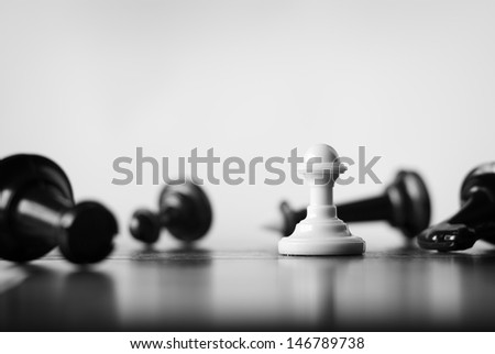 Single white pawn on a chess board surrounded by a number of fallen black chess pieces with selective focus - stock photo