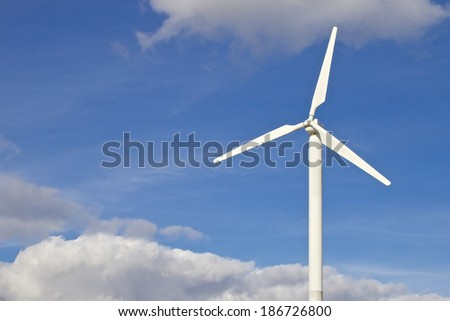 Single white wind turbine in front of a blue and slightly cloudy sky