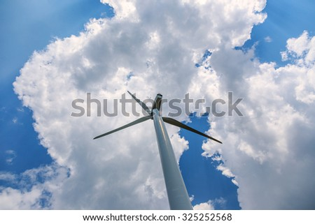 single wind turbine low angle against blue sky with clouds - stock photo