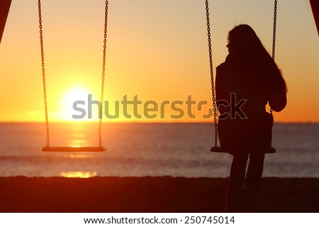 Single woman alone swinging on the beach and looking the other seat missing a boyfriend - stock photo