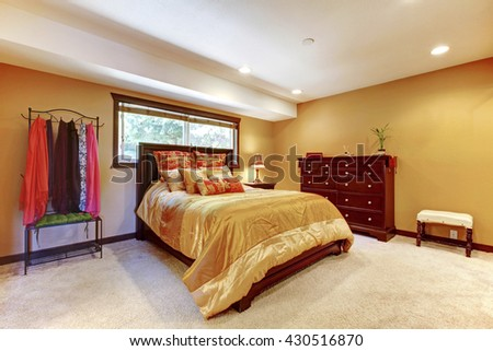 Single woman Asian bedding master bedroom interior with yellow walls. - stock photo