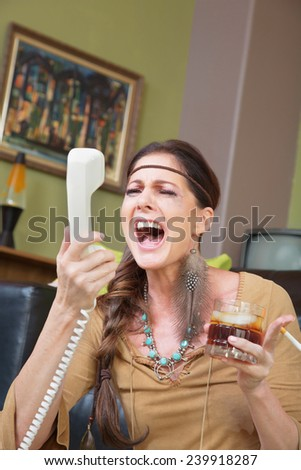 Single woman with drink singing into telephone