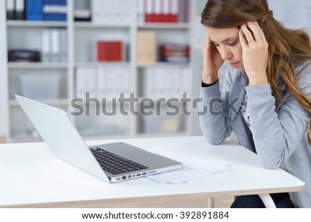 Single woman with long brown hair and gray sweater in pain with hands on head at desk in front of laptop and papers in office with copy space - stock photo