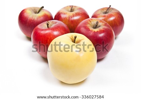 Single yellow apple in front of group of red apple. Group of juicy ripe fruits.  Isolated on white background.