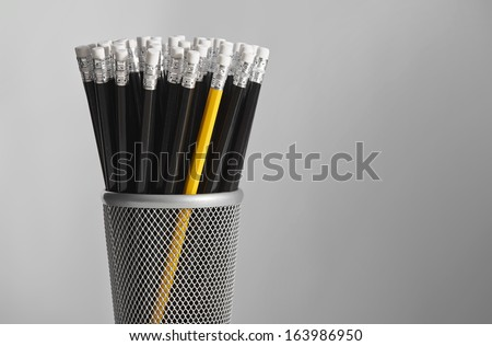 Single yellow pencil in pot of black pencils. - stock photo