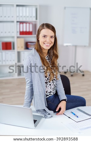 Single young female adult in long brown hair and gray sweater smiling while sitting on desk in office with display and bookshelf in background - stock photo