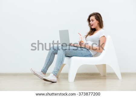 single young woman sitting on a white chair with laptop in an empty room and smiling, thinking on something - stock photo
