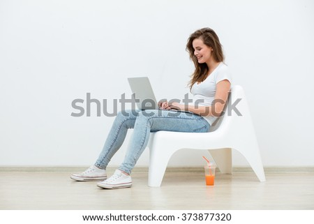single young woman sitting on a white chair with laptop in an empty room chating, thinking on something - stock photo