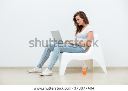single young woman sitting on a white chair with laptop in an empty room looking for a job, thinking on something - stock photo