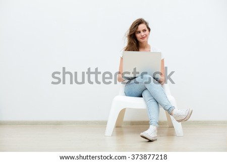 single young woman sitting on a white chair with laptop in an empty room, thinking on something - stock photo
