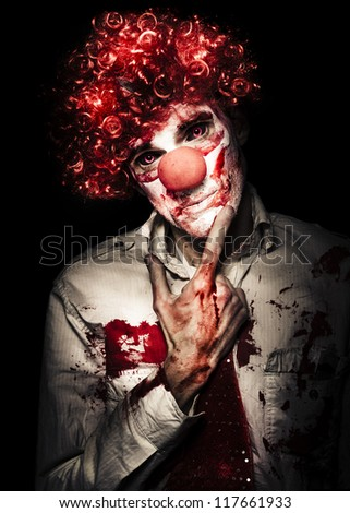 Sinister Bloodstained Clown In A Curly Red Wig Standing Pensively Contemplating His Next Murder Victim With A Dispassionate Look, Halloween Horror Concept