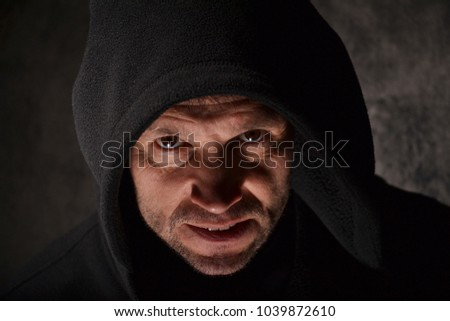 Sinister man wearing hoodie against a dark background.