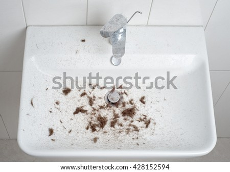 sink after hair cut with trimmer, full of hair - stock photo