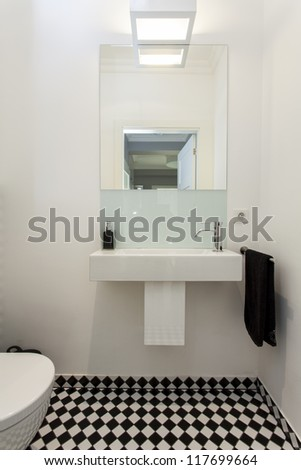 Sink and mirror in toilet, modern house - stock photo
