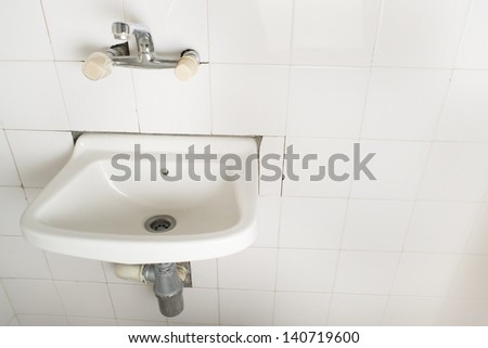 Sink and pipes. Old bathroom - stock photo