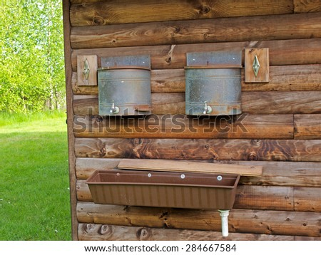 Sink and water tanks with taps on log house wall for washing outdoor  - stock photo