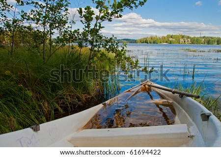 Sink boat on lake shore in Finland