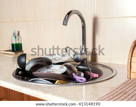 sink full with dirty dishes - stock photo