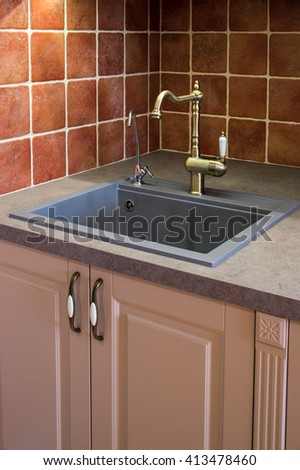 sink on the kitchen surfaces with a bronze crane - stock photo
