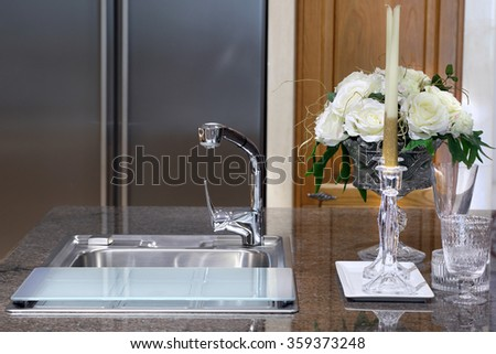 Sink with glass and candlestick on marble table in modern kitchen room. - stock photo
