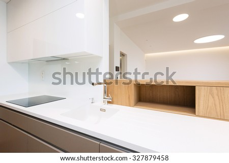 Sink with tap and induction cooker on white worktop of contemporary kitchen - stock photo