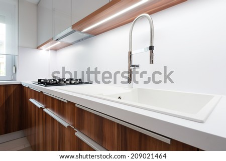 Sink with tap on white worktop in contemporary kitchen - stock photo