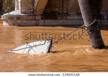 Sinking boat chained to a tree being dragged by the water. - stock photo