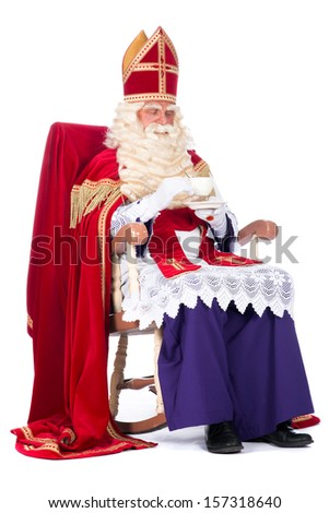 Sinterklaas is resting on his chair, drinking a cup of coffee