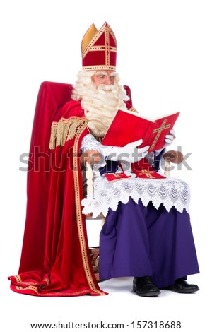 Sinterklaas is resting on his chair, reading in his book